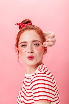 Selbstbewusstes ingwermädchen mit augenklappen, die kamera betrachten. studioaufnahme der freudigen kaukasischen frau, die mit küssendem gesichtsausdruck auf rosa hintergrund aufwirft.