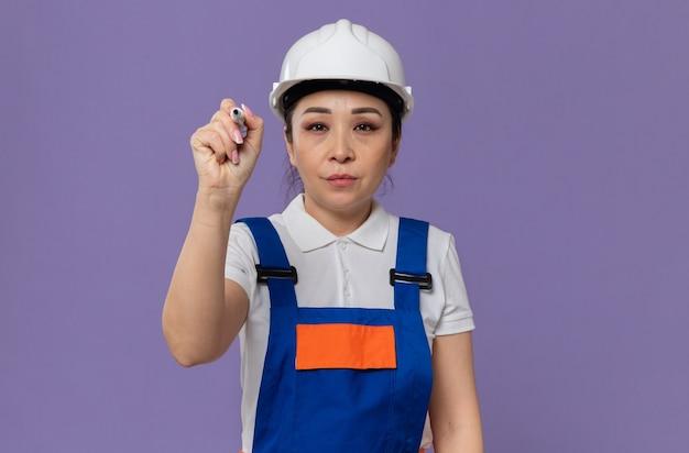 Selbstbewusstes junges asiatisches baumeistermädchen mit weißem schutzhelm, der marker hält