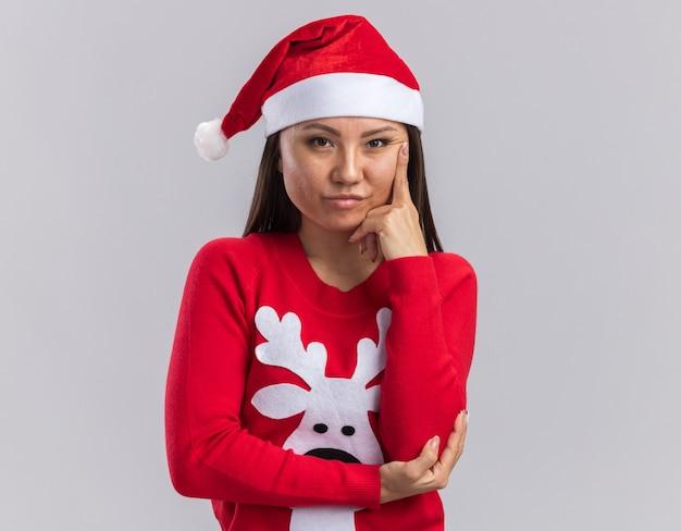 Selbstbewusstes junges asiatisches mädchen mit weihnachtsmütze mit pullover, das den finger auf die wange legt, isoliert auf weißem hintergrund