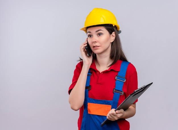 Selbstbewusstes junges baumeistermädchen spricht am telefon und hält zwischenablage auf lokalem weißem hintergrund mit kopienraum