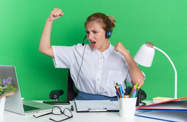 Selbstbewusstes junges blondes call-center-mädchen mit headset, das am schreibtisch mit arbeitswerkzeugen sitzt und auf den laptop schaut, der eine starke geste isoliert auf grüner wand macht