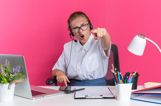 Selbstbewusstes junges blondes callcenter-mädchen mit headset und brille, das am schreibtisch mit arbeitswerkzeugen sitzt und auf die kamera zeigt