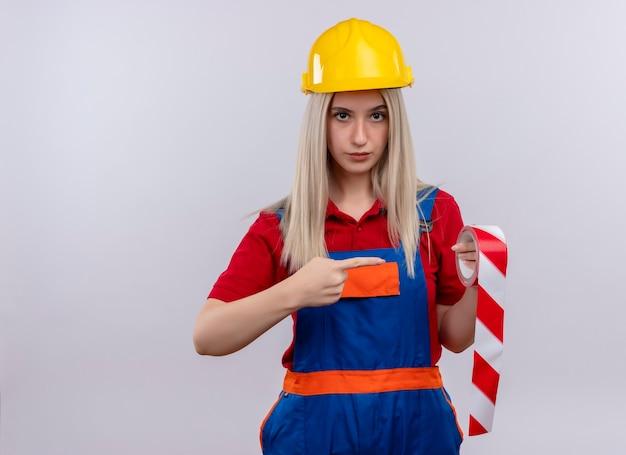 Selbstbewusstes junges blondes ingenieur-baumeistermädchen in der uniform, die klebeband hält, das auf lokalisiertem weißen raum mit kopienraum zeigt