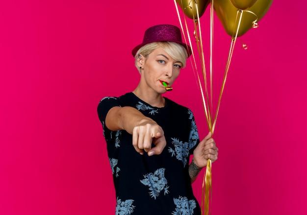 Selbstbewusstes junges blondes partygirl, das partyhut trägt, der ballons und partygebläse im mund hält und auf kamera lokalisiert auf purpurrotem hintergrund mit kopienraum zeigt