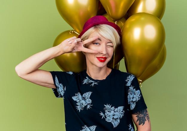 Selbstbewusstes junges blondes partygirl, das partyhut trägt, der vor ballons steht, die friedenszeichen tun und an kamera lokalisiert auf olivgrünem hintergrund zwinkert