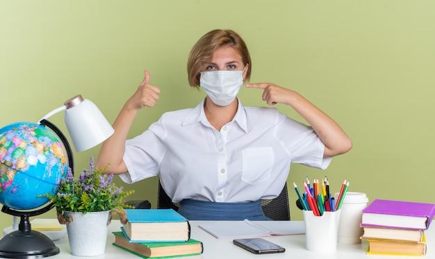 Selbstbewusstes junges blondes studentenmädchen mit schutzmaske, das am schreibtisch sitzt, mit schulwerkzeugen, die auf die maske zeigen, die den daumen nach oben zeigt