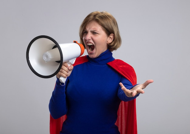 Selbstbewusstes junges blondes superheldenmädchen im roten umhang, der im lautsprecher schreit, der leere hand zeigt, die seite lokalisiert auf weißem hintergrund betrachtet