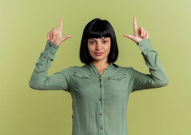 Selbstbewusstes junges brünettes kaukasisches mädchen zeigt mit zwei händen, die kamera lokalisiert auf olivgrünem hintergrund mit kopienraum betrachten