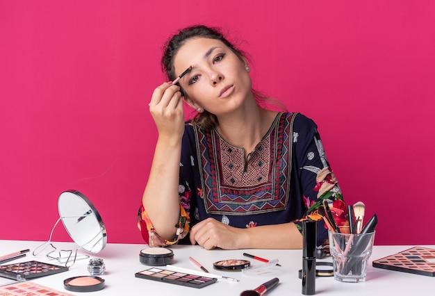 Selbstbewusstes junges brünettes mädchen, das am tisch mit make-up-tools sitzt, die lidschatten mit make-up-pinsel auftragen