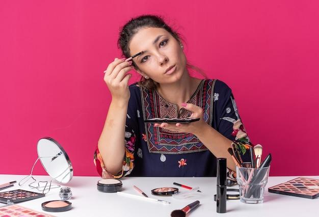 Selbstbewusstes junges brünettes mädchen, das am tisch mit make-up-tools sitzt, die lidschatten-palette hält und lidschatten mit make-up-pinsel aufträgt