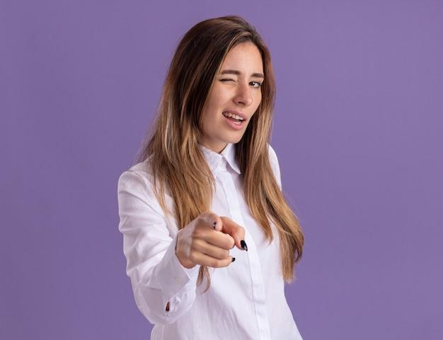 Selbstbewusstes junges hübsches kaukasisches mädchen blinzelt mit den augen und zeigt auf die kamera, die auf lila wand mit kopienraum isoliert ist