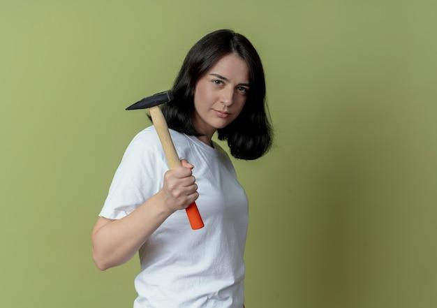 Selbstbewusstes junges hübsches kaukasisches mädchen, das im profilansicht hält hammer lokalisiert auf olivgrünem hintergrund mit kopienraum steht