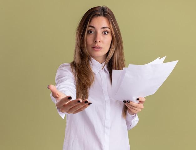 Selbstbewusstes junges hübsches kaukasisches mädchen, das leere papierblätter hält und die hand isoliert auf olivgrüner wand mit kopienraum ausstreckt