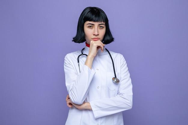 Selbstbewusstes junges hübsches kaukasisches mädchen in arztuniform mit stethoskop, das die hand auf ihr kinn legt und nach vorne schaut
