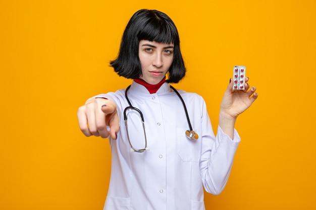 Selbstbewusstes junges hübsches kaukasisches mädchen in arztuniform mit stethoskop, das nach vorne zeigt und tablettenverpackung hält