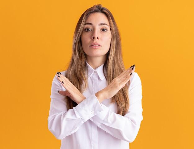 Selbstbewusstes junges hübsches kaukasisches mädchen kreuzt die hände und gestikuliert kein zeichen isoliert auf oranger wand mit kopienraum