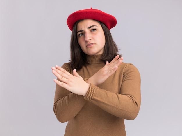 Selbstbewusstes junges hübsches kaukasisches mädchen mit baskenmütze, das die hände kreuzt und kein zeichen gestikuliert