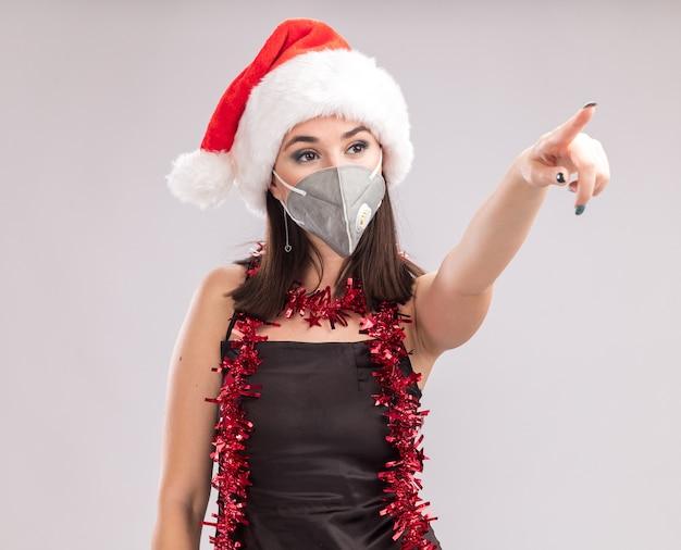 Selbstbewusstes junges hübsches kaukasisches mädchen mit weihnachtsmütze und schutzmaske lametta girlande um den hals, das auf die seite isoliert auf weißem hintergrund zeigt