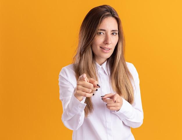 Selbstbewusstes junges hübsches kaukasisches mädchen zeigt mit zwei händen auf die kamera