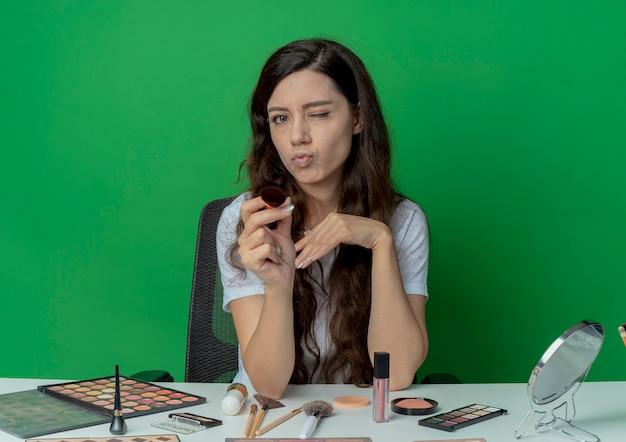 Selbstbewusstes junges hübsches mädchen, das am make-up-tisch mit make-up-werkzeugen sitzt, die errötenden pinsel halten und auf kamera mit ihm lokalisiert auf grünem hintergrund zeigen
