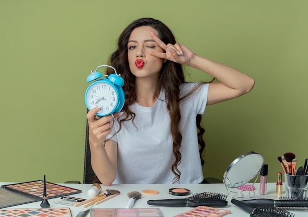 Selbstbewusstes junges hübsches mädchen, das am make-up-tisch mit make-up-werkzeugen sitzt, die wecker halten, der zwinkert und friedenszeichen tut und kamera durch finger lokalisiert auf olivgrünem hintergrund betrachtet
