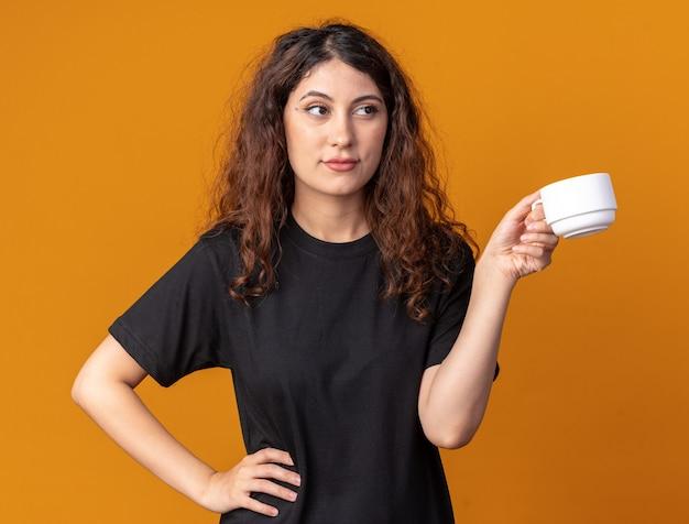 Selbstbewusstes junges hübsches mädchen, das eine tasse tee hält und die hand auf der taille hält und auf die seite schaut