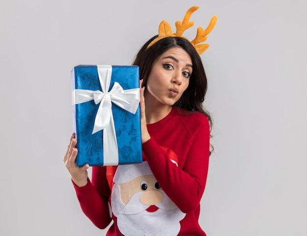 Selbstbewusstes junges hübsches mädchen, das rentiergeweih-stirnband und weihnachtsmannpullover trägt, der weihnachtsgeschenkpaket hält, das mit gespitzten lippen schaut