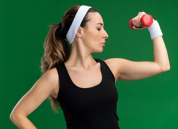Selbstbewusstes junges, hübsches, sportliches mädchen mit stirnband und armbändern, das die hantel hebt und die hand auf der taille hält und eine starke geste macht, die ihre muskeln betrachtet