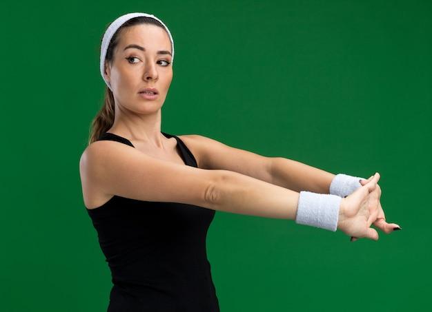Selbstbewusstes junges hübsches sportliches mädchen mit stirnband und armbändern