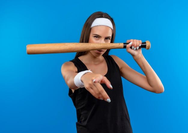 Selbstbewusstes junges hübsches sportliches mädchen mit stirnband und armband, das baseballschläger hält und isoliert auf blaue wand zeigt