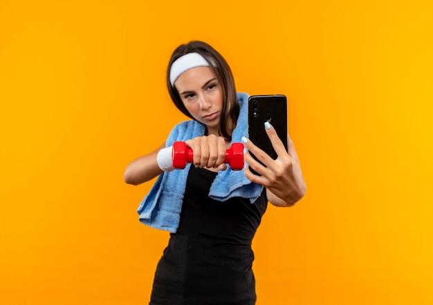 Selbstbewusstes junges hübsches sportliches mädchen mit stirnband und armband, das das handy ausstreckt, das eine hantel mit einem handtuch um den hals hält, isoliert auf der orangefarbenen wand