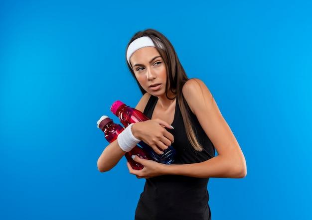 Selbstbewusstes junges hübsches sportliches mädchen mit stirnband und armband, das wasserflaschen hält und die seite isoliert auf blauer wand betrachtet