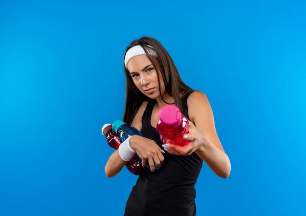 Selbstbewusstes junges hübsches sportliches mädchen mit stirnband und armband, das wasserflaschen isoliert auf blauer wand hält und ausstreckt