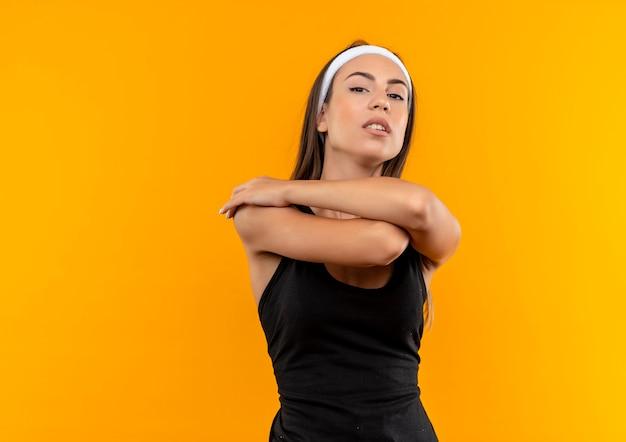 Selbstbewusstes junges hübsches sportliches mädchen mit stirnband und armband mit verschränkten armen an oranger wand