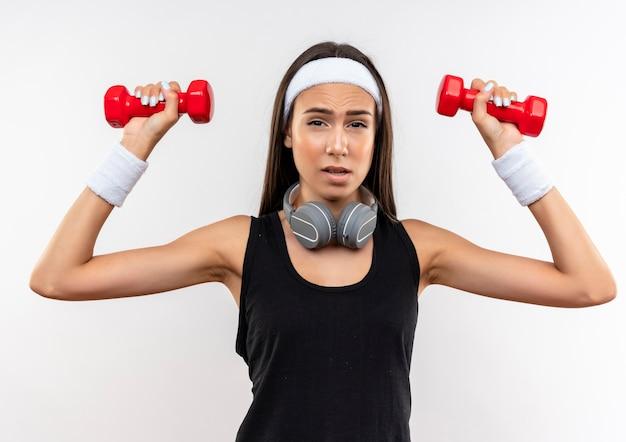 Selbstbewusstes junges hübsches sportliches mädchen mit stirnband und armband und kopfhörern am hals, das hanteln isoliert auf weißer wand hebt