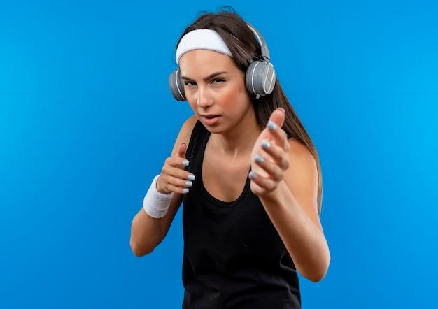 Selbstbewusstes junges hübsches sportliches mädchen mit stirnband und armband und kopfhörern, die die hände einzeln auf blauer wand ausstrecken