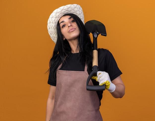 Selbstbewusstes junges kaukasisches gärtnermädchen, das uniform und hut mit gärtnerhandschuhen trägt, die spaten isoliert auf oranger wand mit kopierraum halten