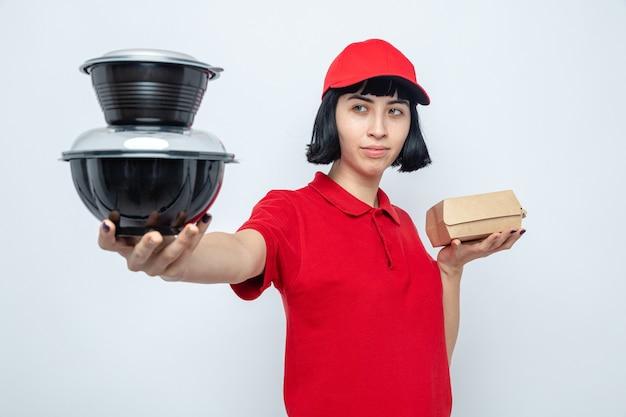 Selbstbewusstes junges kaukasisches liefermädchen, das lebensmittelbehälter und -verpackungen hält