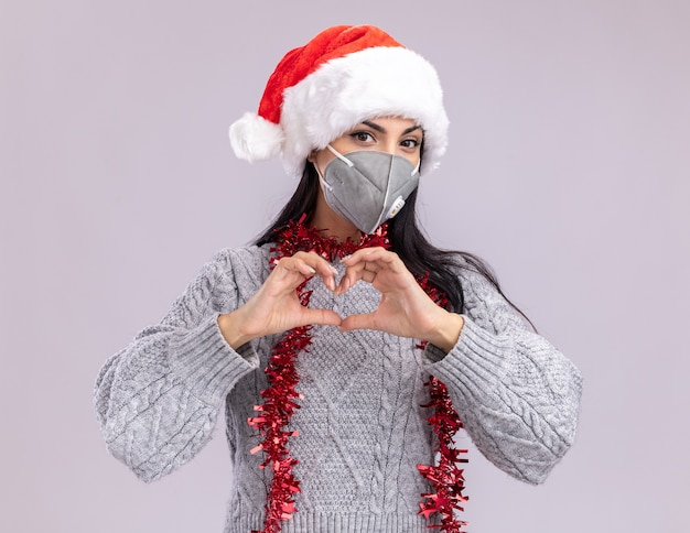 Selbstbewusstes junges kaukasisches mädchen, das weihnachtshut und lametta-girlande um hals mit schutzmaske trägt, die kamera tut, die herzzeichen lokalisiert auf weißem hintergrund betrachtet