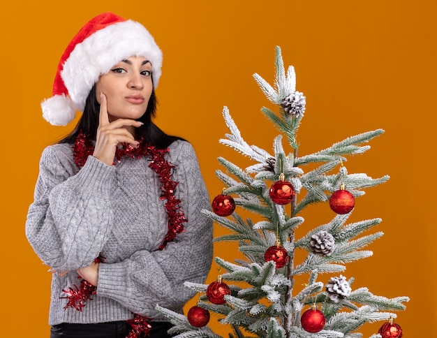 Selbstbewusstes junges kaukasisches mädchen, das weihnachtsmütze und lametta-girlande um den hals trägt, der nahe verziertem weihnachtsbaum steht und kamera betrachtet, die hand auf kinn lokalisiert auf orange hintergrund hält