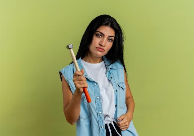 Selbstbewusstes junges kaukasisches mädchen hält hammer