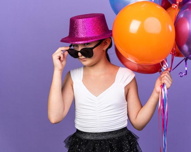 Selbstbewusstes junges kaukasisches mädchen in sonnenbrille mit violettem partyhut, der heliumballons hält und isoliert auf lila wand mit kopierraum schaut