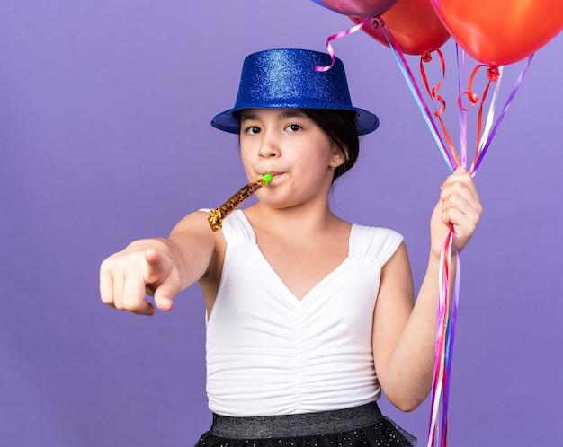 Selbstbewusstes junges kaukasisches mädchen mit blauem partyhut, der heliumballons hält und partypfeife bläst, die isoliert auf lila wand mit kopienraum zeigt