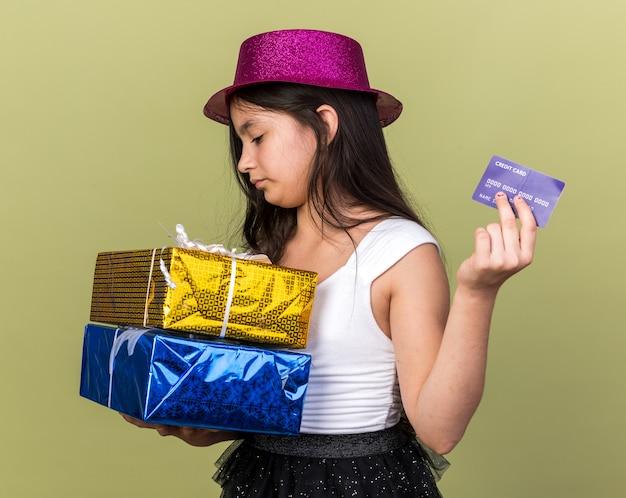 Selbstbewusstes junges kaukasisches mädchen mit lila partyhut, das kreditkarte hält und geschenkboxen einzeln auf olivgrüner wand mit kopienraum betrachtet