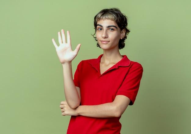 Selbstbewusstes junges kaukasisches mädchen mit pixie-haarschnitt, der fünf mit der hand lokalisiert auf olivgrünem hintergrund mit kopienraum zeigt