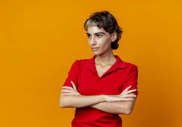 Selbstbewusstes junges kaukasisches mädchen mit pixie-haarschnitt stehend mit geschlossener haltung, die seite lokalisiert auf orange hintergrund mit kopienraum betrachtet