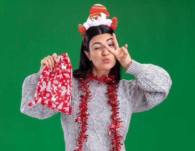 Selbstbewusstes junges kaukasisches mädchen mit weihnachtsmann-stirnband und lametta-girlande um den hals, das einen weihnachtsgeschenksack hält und ein friedenszeichen vor dem auge macht, das isoliert auf grüner wand zwinkert?