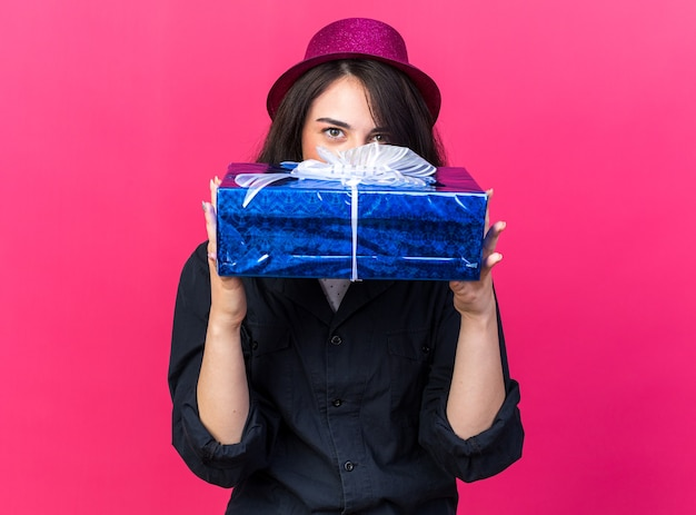 Selbstbewusstes junges kaukasisches partymädchen mit partyhut, das geschenkpaket von hinten isoliert auf rosa wand hält