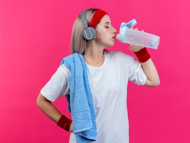 Selbstbewusstes junges kaukasisches sportliches mädchen mit hosenträgern an kopfhörern, das stirnband und armbänder trägt, hält ein handtuch auf der schulter und trinkt aus einer wasserflasche