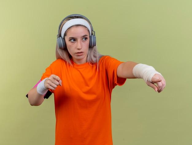 Selbstbewusstes junges kaukasisches sportliches mädchen mit hosenträgern auf kopfhörern mit stirnband-armbändern und telefonarmband sieht und zeigt seitlich